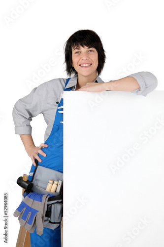 Female DIY person stood with blank poster