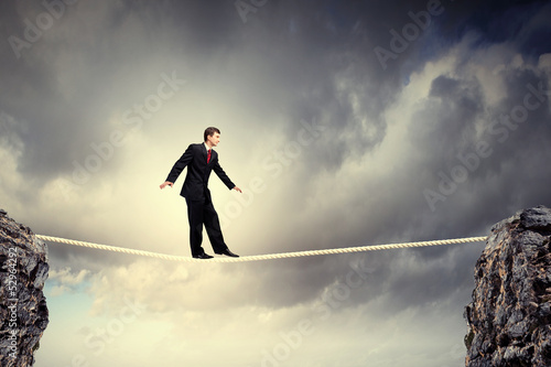 Businessman balancing on rope