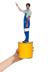 Male decorator standing on giant paint tin