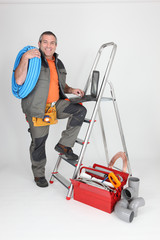 Labourer climbing step-ladder