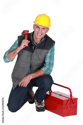 Smiling plumber with his toolbox on white background