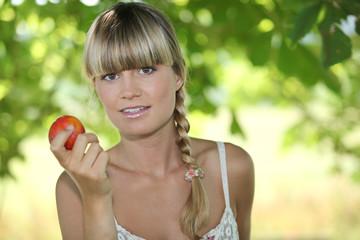 Blond woman in garden holding apple