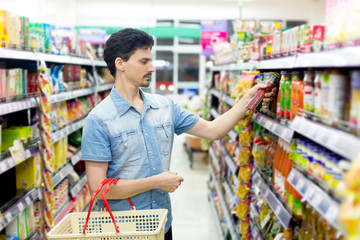A man in a supermarket to buy ketchup