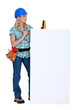 Female electrician with blank poster
