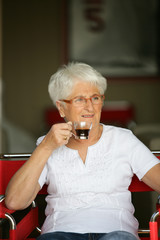 Elderly woman drinking a cup of coffee