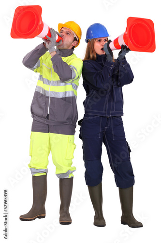 A team of tradespeople yelling into pylons