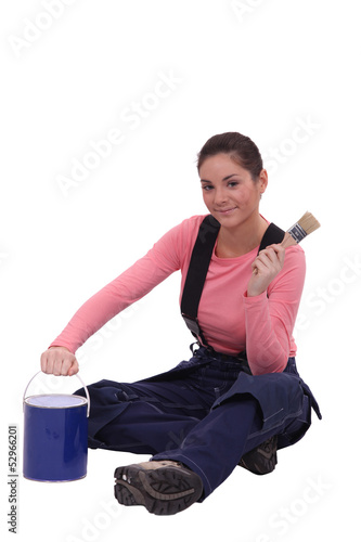 female painter holding a can and a brush