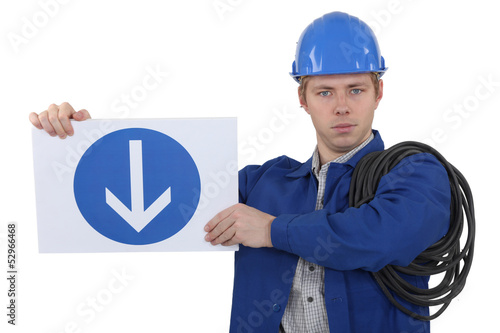 Electrician holding road sign