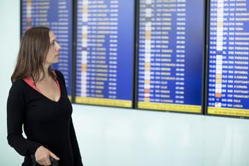 Frau wartet vor einer Anzeigetafel am Flughafen