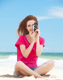 Redhead teen girl with retro camera on the beach