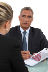 Boss explaining financial results to female employee