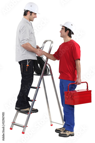 Two workers greeting each other with a hand-shake