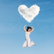 Asian woman jumping under heart cloud