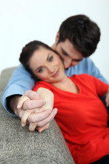 Couple holding hands on a sofa
