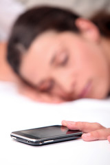 Woman asleep next to mobile telephone