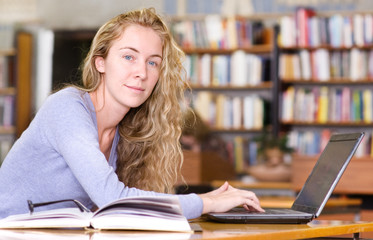 female student with laptop working in library. looking at camera