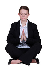 Young businesswoman meditating