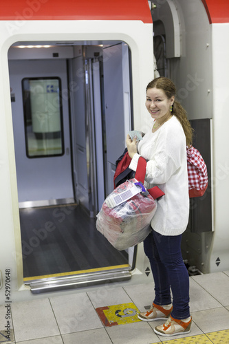 Leinwanddruck Bild Attractive woman a passenger with bags boarding express