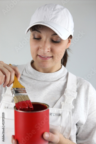 female painter with red tin of paint and brush