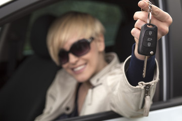 happy girl sitting in her new car and shows the keys