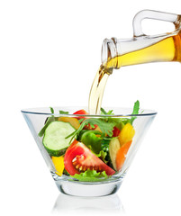 Salad with olive oil pouring from a bottle on white background.