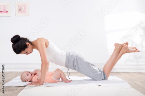 Tuinposter Gymnastiek mother does gymnastics with her baby