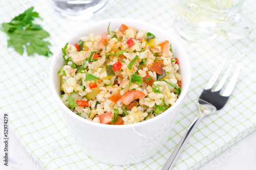 white bowl of salad with bulgur, zucchini, tomatoes and parsley