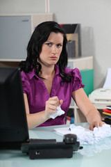 Angry woman crumpling papers