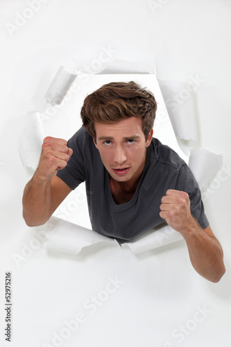 Young man punching his way through a barrier