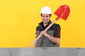 Happy mason stood by wall