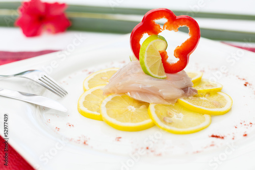 Fish Carpaccio on lemon slices decorated with bell pepper slice
