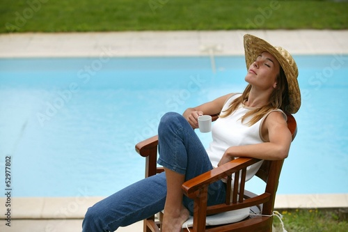 Woman sat poolside in straw hat