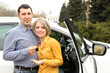 Portrait of happy beautiful couple with car keys, standing near