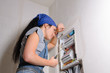 Female electrician with open fuse box