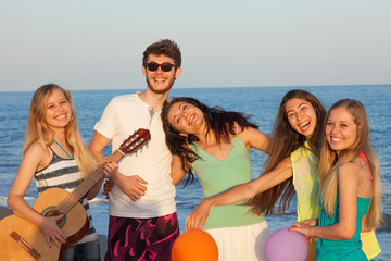 Group of young people enjoying beach party with playing guitar a