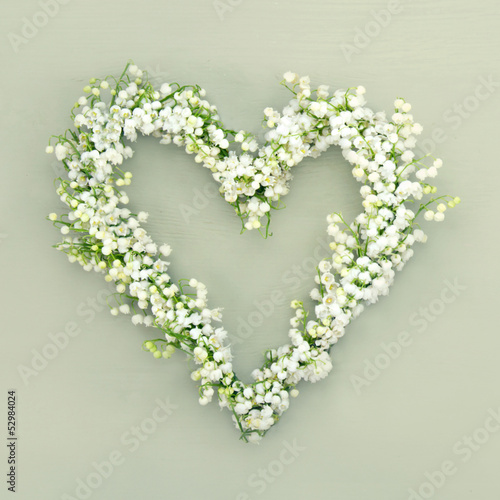 Foto op Plexiglas Lelietje van dalen Heart shaped flower wreath on green background