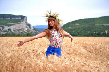 The girl on a field with wheat ears