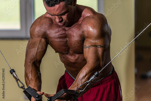body builder doing standing press white cable for chest