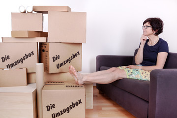Woman sitting on the sofa in front of their moving boxes packed