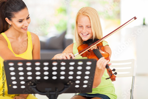 pre teen girl enjoying her violin lesson