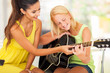 beautiful music teacher tutoring young girl to play guitar