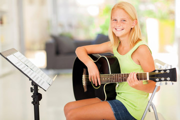 preteen girl practicing guitar