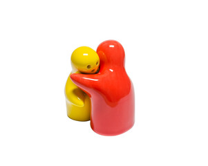 Abstract image of ceramic dolls in different color embrace