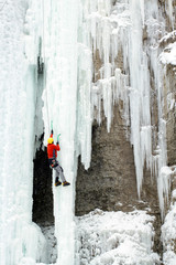Ice climber struggles up a frozen waterfall.