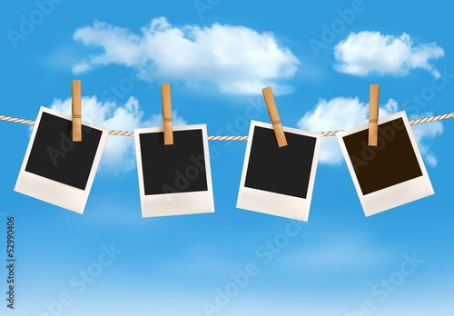 Background with photos hanging on a rope in front of a blue sky