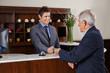 Rezeptionist im Hotel gibt Senior Schlüsselkarte