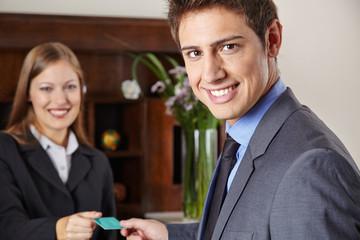 Geschäftsmann im Hotel bekommt Schlüsselkarte