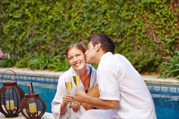 Paar trinkt Sekt am Pool