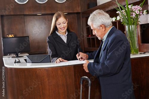 Gast unterschreibt Formular im Hotel