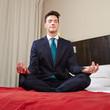 Geschäftsmann macht Yoga im Hotel
